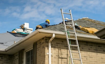 Roof worker installing new shingles