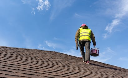 Workman standing on tile roof